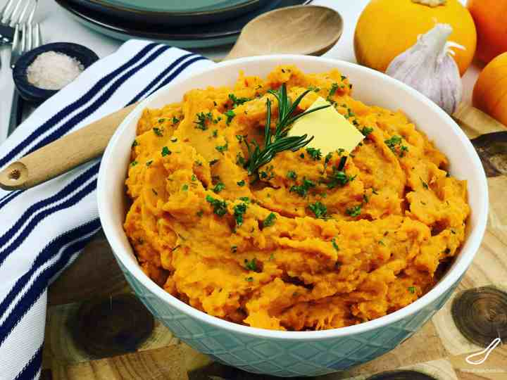 Mashed Sweet Potatoes with rosemary and butter in a bowl on the table