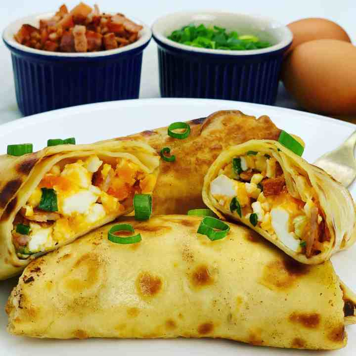 Delicious Breakfast Crepes stuffed with boiled eggs, bacon, cheese and green onions before being pan fried in butter. Generously slathered in sour cream - these savory crepes are worth the effort!