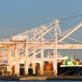 Oakland Commercial port at dusk. Cranes loading containers on a commercial ship.