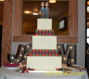 Wedding cake, topped with custom-made figures of the grooms