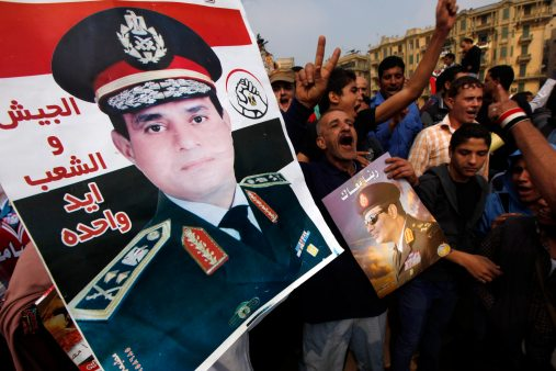 Supporters of Egypt's army chief General Abdel Fattah al-Sisi hold up a poster of Sisi at Tahrir square in downtown Cairo