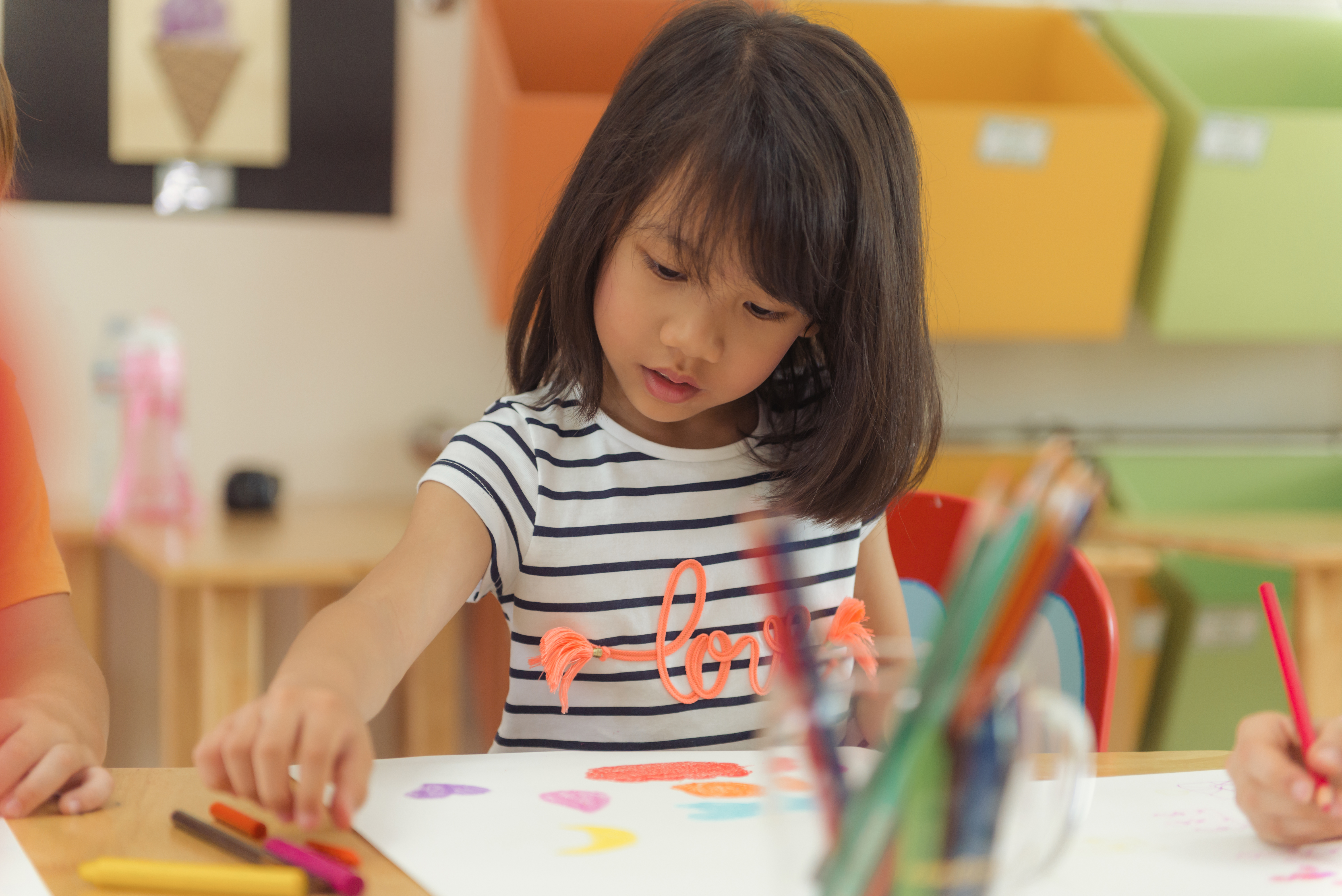 Girl drawing color pencils in kindergarten classroom, preschool and kid education concept, Vintage effect style pictures.