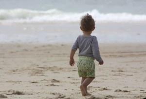 Bébé sur la plage faisant face à la mer