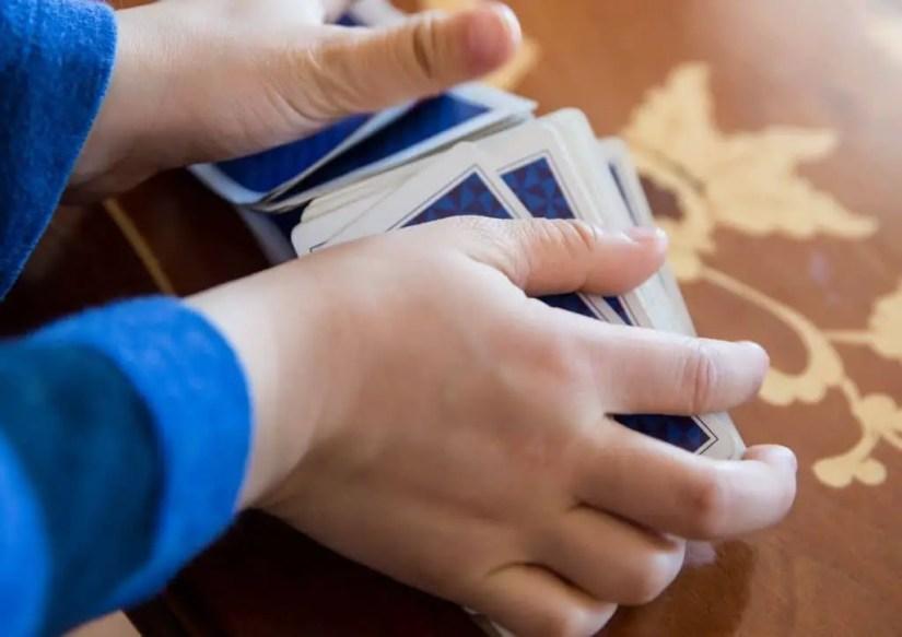 Main d'enfant en train de mélanger un jeu de cartes