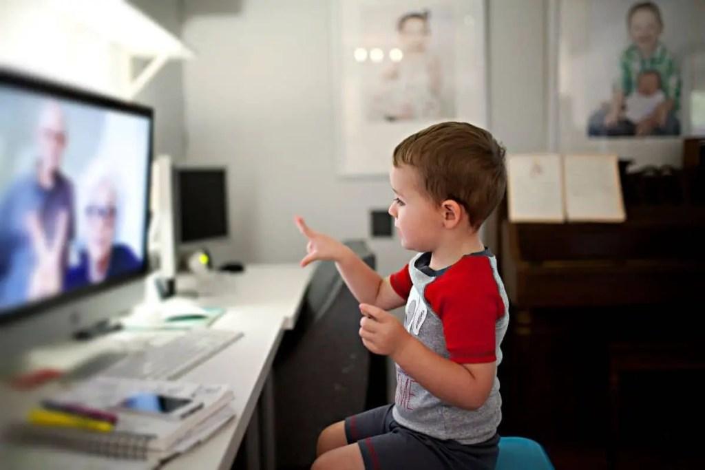 La technologie au service de la relation grands-parents petits-enfants : un jeune garçon en train d'échanger avec sa famille via un écran d'ordinateur