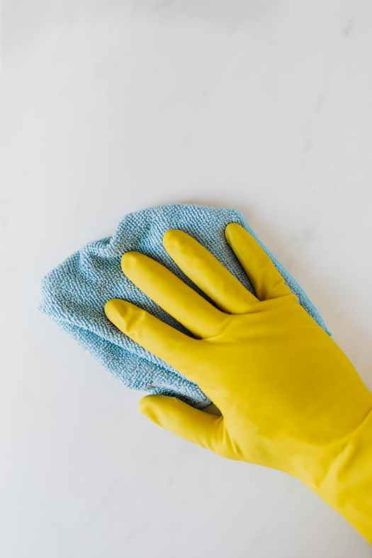 crop unrecognizable person in yellow gloves cleaning white surface