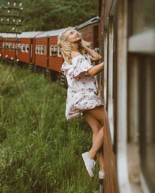 optimistic girl leaning out from wagon exit of train