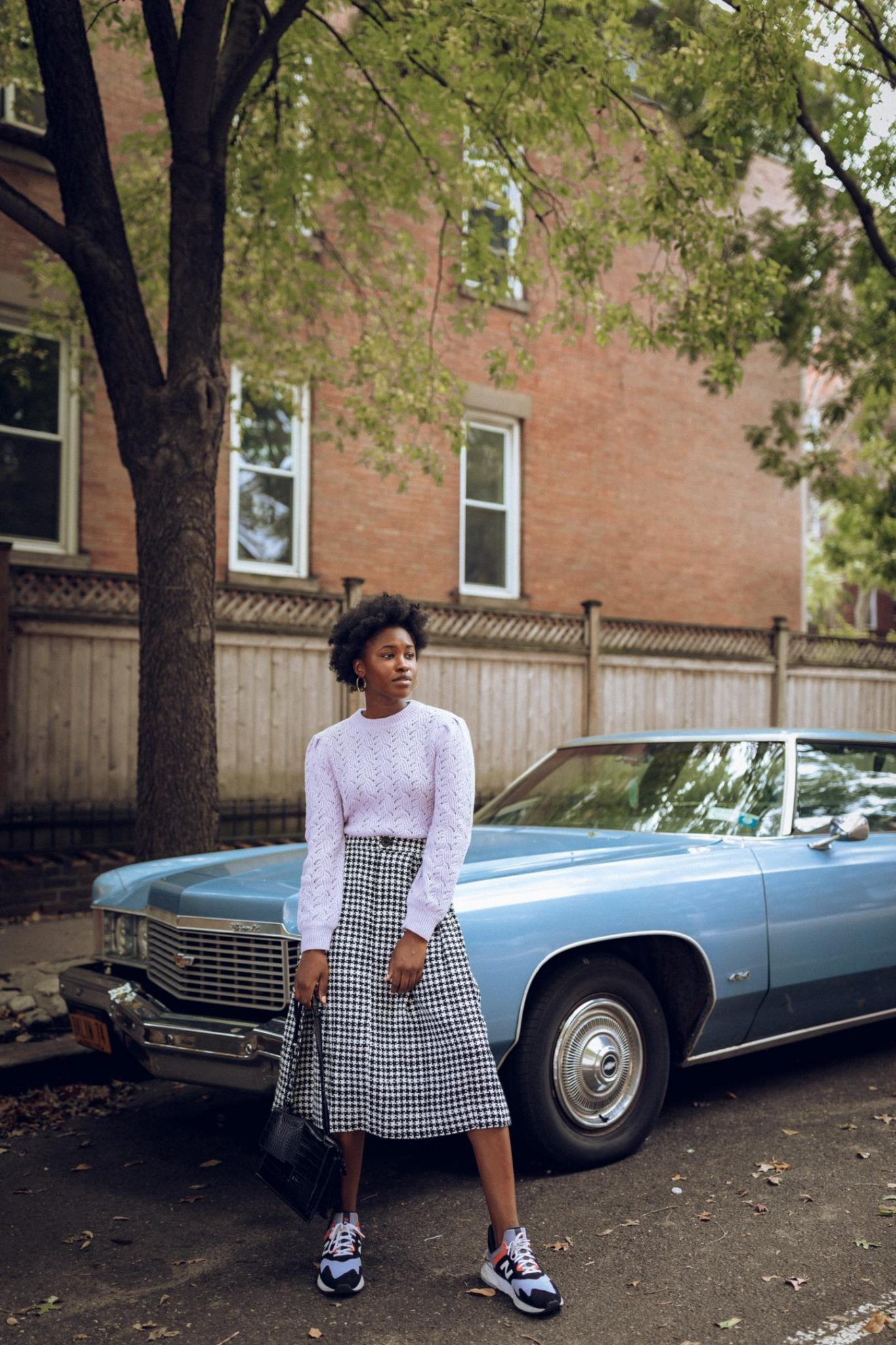 Black Women standing in front of a vintage car