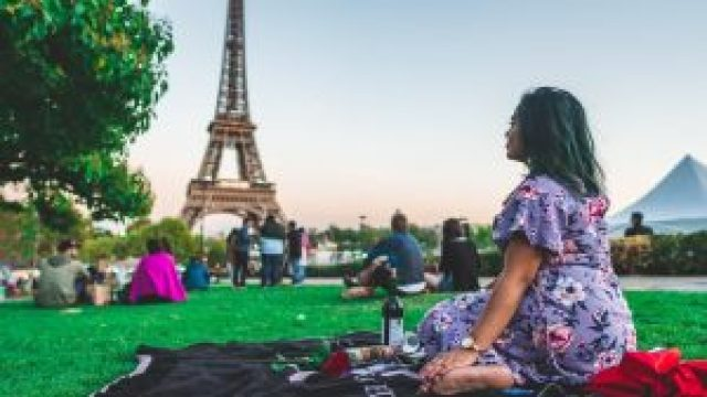 Femme assise parterre, elle fait un pique-nique devant la Tour Eiffel