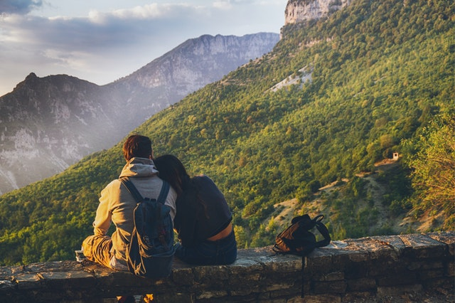 un homme et une femme assis qui regardent la vue sur les montagnes