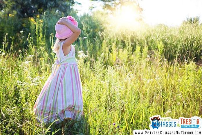 un fille regarde un couché de soleil dans un champ