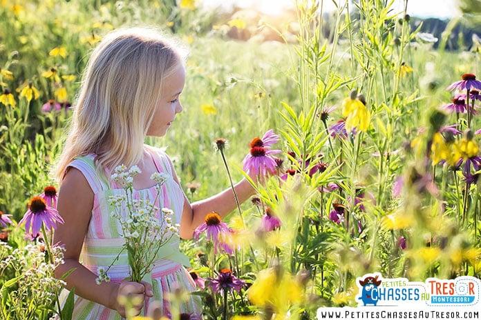 une enfant ramasse des fleurs dans un champs