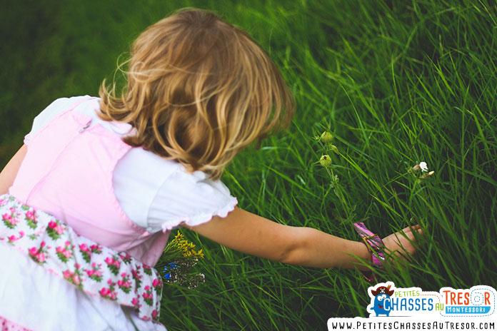 un enfants passe la main dans l'herbe verte