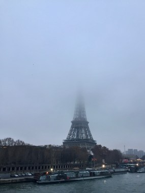 The Eiffel Tower and the sun and fog set.