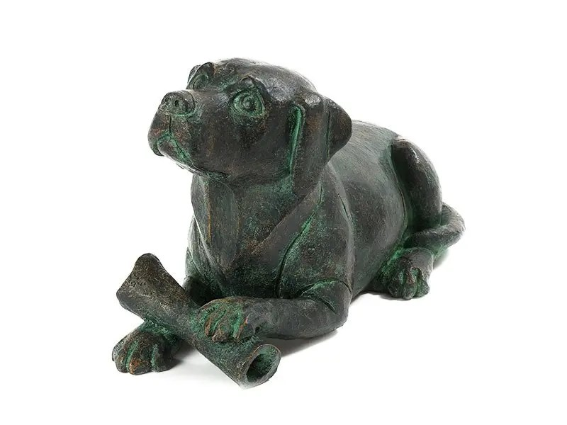 Figurine dog urn for pet dog ashes. Depicting a dog lying down with a bone in an aged bronze style. Personalizable.