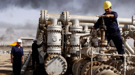 FILE - In this Dec. 13, 2009 file photo, Iraqi laborers work at the Rumaila oil refinery in Zubair near the city of Basra, Iraq. Across a Mideast fueled by oil production, low global prices have some countries running on empty and scrambling to cover shortfalls, even as more regional crude is on tap to enter the market.(AP Photo/Nabil al-Jurani, File)