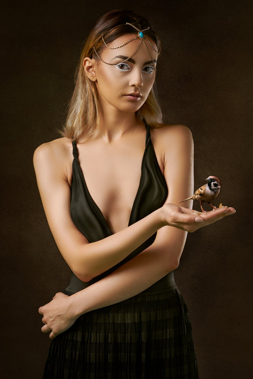 photo of woman holding brown bird