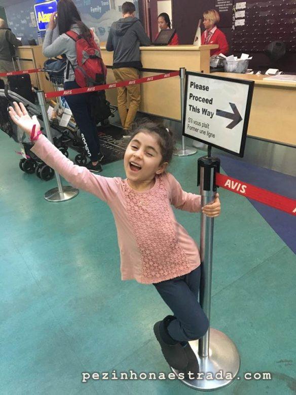 Depois de dois longos voos, a Bela continua toda animada, aguardando o carro na Avis do terminal do aeroporto em Vancouver.