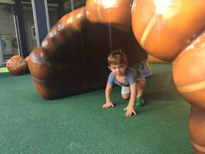 O Felipe embaixo de uma luva de baseball gigante, na área infantil do Yankee Stadium, no Bronx, NY