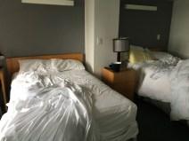 As camas estão bagunçadas, mas dá para ter uma ideia do tamanho do quarto.