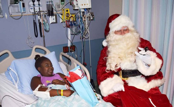 Santa visits with Nicole Beecham, 11, in the pediatrics ward at the University Hospital of Northern B.C. Wednesday. Nicole says she should be home in time for Christmas. Bill Phillips photo