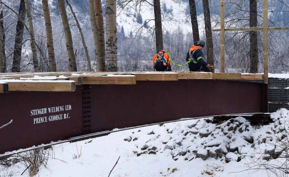 Workers install decking and ramps on the new footbridge in Cottonwood Island Park. Bill Phillips photo