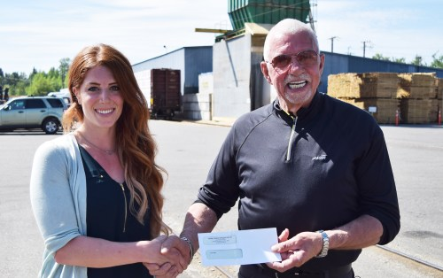 John Brink, of the Brink Group of Companies, purchases $300 of Bassy's Bicuits, from Laura Bass. The dog biscuits will be donated to the SPCA. Bill Phillips photo