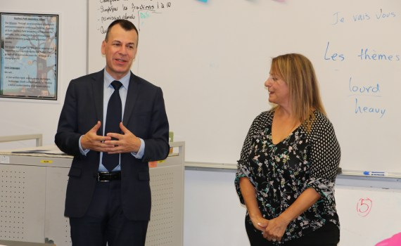 Philippe Sutter, Consul General of France, left, stands with Duchess Park teacher Josie Nielson while addressing Nielson's Grade 11-12 core French students. School District 57 photo