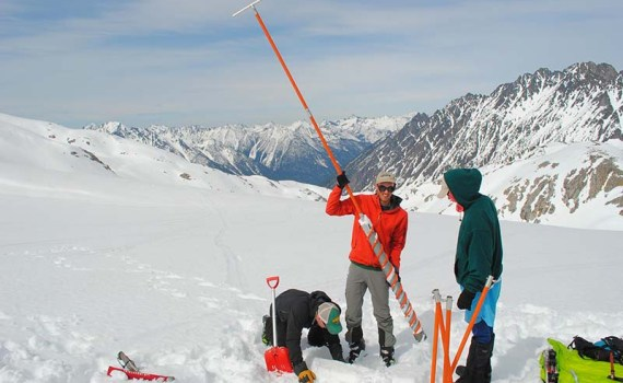 Ben Pelto holding the snow corer, a device used to take snow or ice cores. All of snow and glacier science reports snow and ice in meters of water equivalent, as researchers need to know how much water the snow holds. Also pictured are Tom Hammond of the University of Washington and Micah May of UNBC. Kokanee Glacier, near Ainsworth in the Kootenays, BC. April 2016. Photo: Jill Pelto