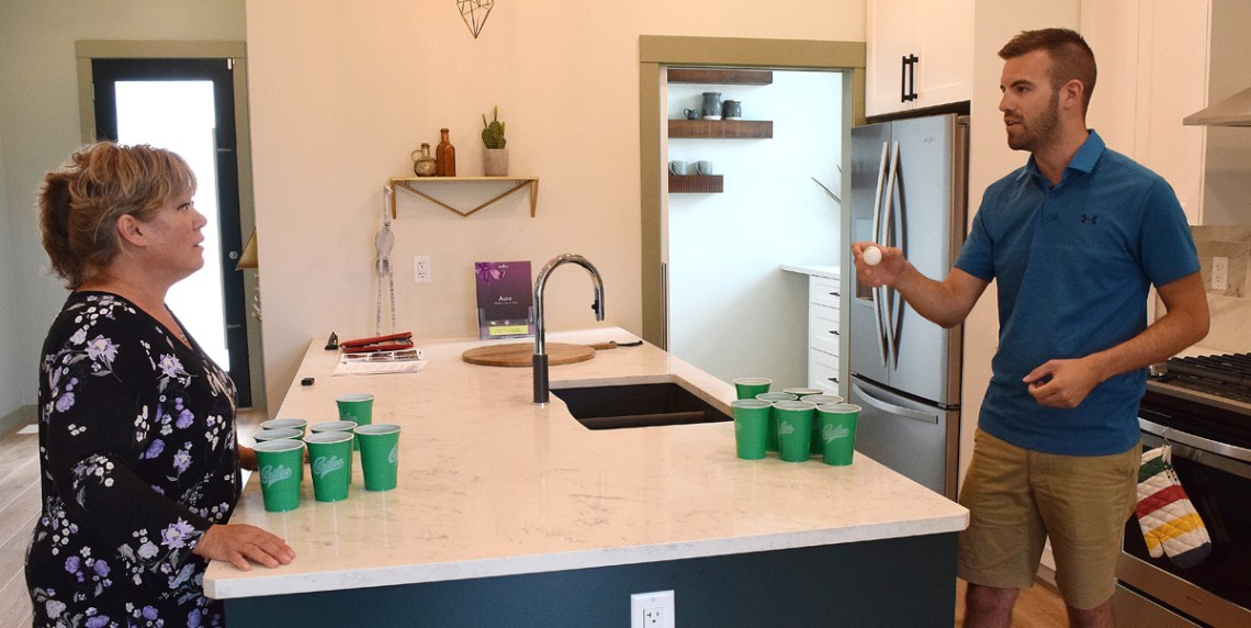 Terri McConnachie and Kyle Sampson play a little beer pong in the kitchen (they promised to clean it up after they left). Actually, they were filming a promotional video for the Hospice Dream Home.