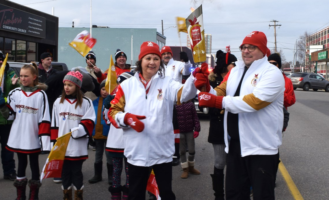 Lheidli TÕenneh edler Darlene McIntosh passes the Roly McLenahan Canada Games Torch to Cariboo-Prince George MP Todd Doherty during Saturday's torch run through downtown. Bill Phillips photo