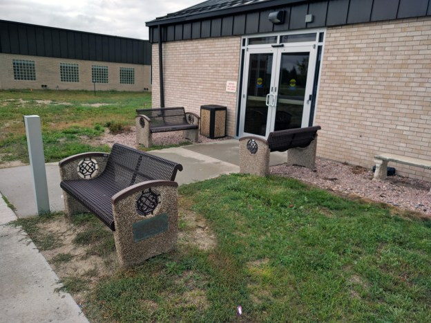 I go in this door. Since the area was torn up for construction, the grass hasn't been dealt with yet, but it will be very nice once they replace the grass. Don't think those benches aren't appreciated!