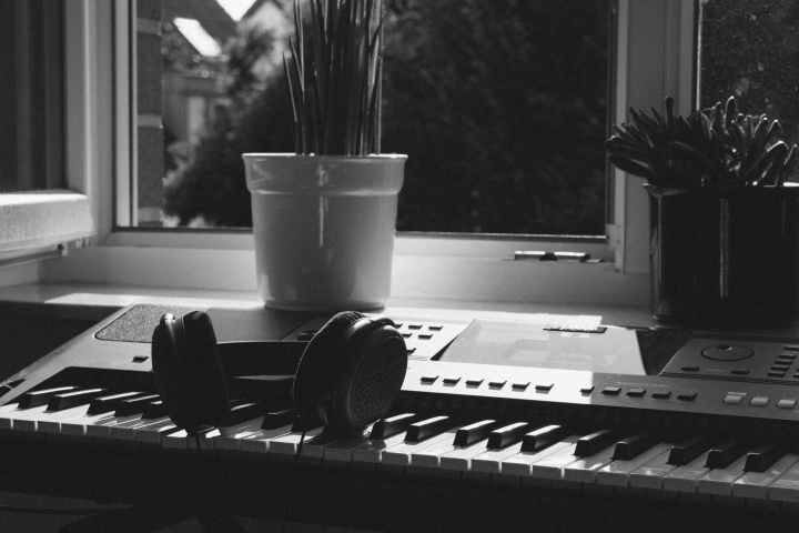 grayscale photography of electronic keyboard near window