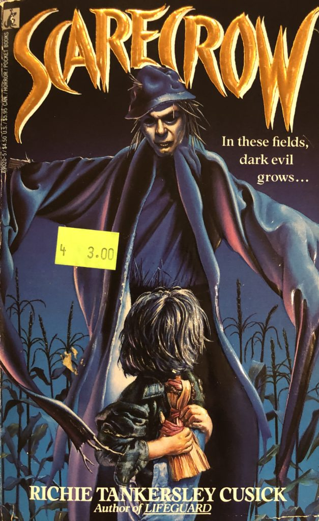 """Book cover for the horror novel """"Scarecrow,"""" with a small child looking back at a scary scarecrow."""