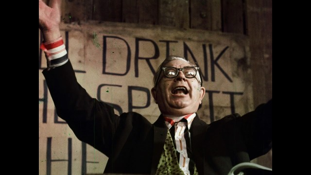 "A still from the movie ""This Stuff'll Kill Ya!"" With a man giving a speech, his arms raised."