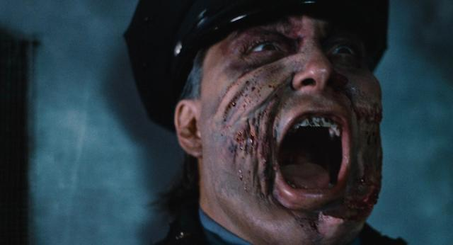Close up of actor Robert Z'Dar as the maniac cop screaming with blood splattered on his face.