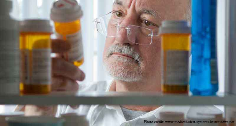 Picture of an elderly man inspecting his medications