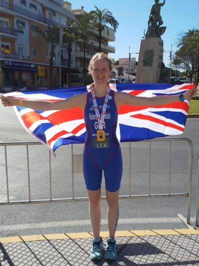 An athlete holding the Union Jack wearing a medal