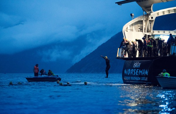 Athletes jumping into the water from a boat at the start of the Norseman Xtri