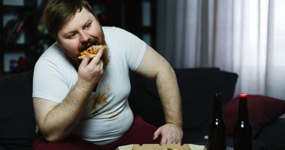 Ugly fat man eats pizza sitting on the sofa