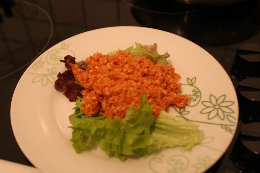 Veganes Mett aus Reiswaffeln auf einem Teller, garniert mit Salat. Wenn man auf das Bild klickt gelangt man zum eiweißarmen Rezept für Menschen mit PKU.
