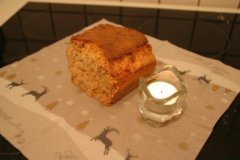 Ein Stück Honigkuchen steht auf einer Serviette mit Weihnachtsmotiv. Daneben eine Kerze. Wenn man auf das Bild klickt gelangt man zum eiweißarmen Rezept für Menschen mit PKU.