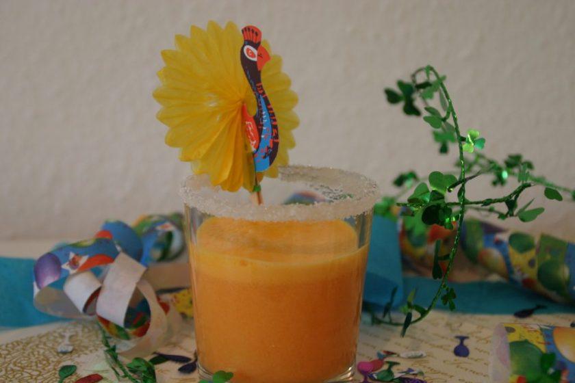 Ein Glas mit orangefarbenem Getränk. Das Glas hat einen Zuckerrand und im Getränk steckt ein Deko-Pfau. Silvesterdekoration im Hintergrund aus Luftschlangen und Kleeblättern. Wenn man auf das Bild klickt gelangt man zum eiweißarmen Rezept für Menschen mit PKU.
