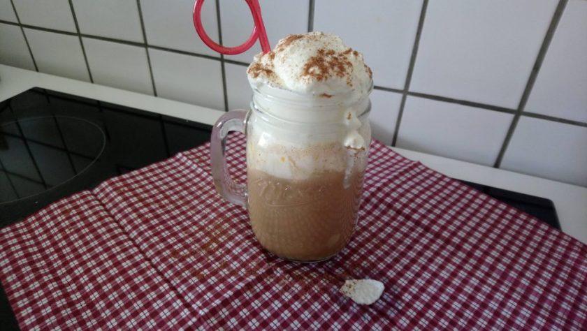 In einem Krug ist ein Kaffeegetränk mit hoher Milchschaumasse und Sahne obenauf zu sehen. Es steckt ein roter geringelter Strohhalm im Getränk. Wenn man auf das Bild klickt gelangt man zum eiweißarmen Rezept für Menschen mit PKU.