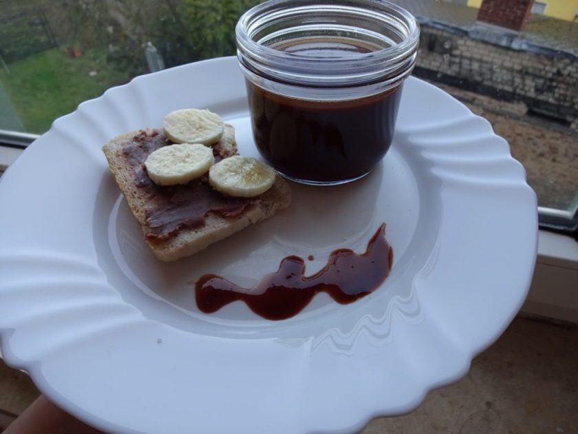 Auf einem weißen Teller liegt ein Brot mit Schokoladenaufstrich und Bananenscheiben. Daneben steht, auf dem Teller, zusätzlich ein Glas mit selbstgemachtem Schokoladenaufstrich. Wenn man auf das Bild klickt gelangt man zum eiweißarmen Rezept für Menschen mit PKU.
