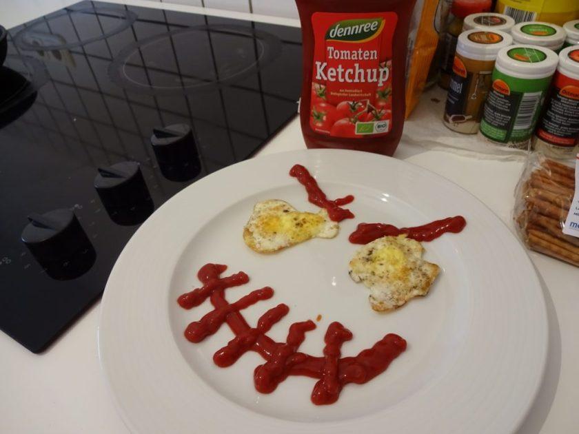 Ein gruseliges Halloween Gesicht aus Ketchup und Ei. Die Augen bilden gebratene Wachteleier und der Mund ist aus Ketchup auf den Teller getropft. Wenn man auf das Bild klickt gelangt man zum eiweißarmen Rezept für Menschen mit PKU.
