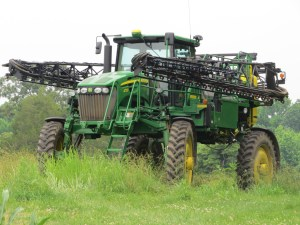 A crop sprayer sitting by the edge of a corn field.