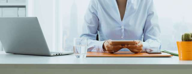 Corporate businesswoman sitting at desk and working with her digital tablet, business and communication concept