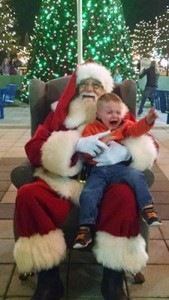 Young boy crying on Santa's lap