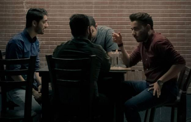Men gathered around a table talking
